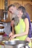 Os pares novos estão cozinhando em casa imagem de stock