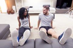 Os pares novos estão treinando fazendo a ginástica em casa fotografia de stock