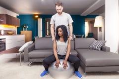 Os pares novos est?o treinando fazendo a gin?stica em casa fotografia de stock royalty free