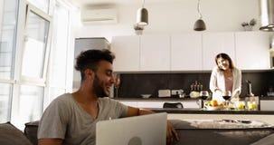 Os pares novos felizes da raça misturada dirigem o interior, homem latino-americano que usa o laptop, mulher asiática que cozinha vídeos de arquivo