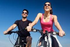 Os pares novos felizes em uma bicicleta montam no campo Fotos de Stock