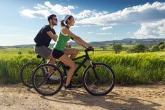 Os pares novos felizes em uma bicicleta montam no campo Imagem de Stock