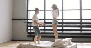 Os pares novos felizes estão saltando na cama que aplaude e que guarda as mãos Conceito do relacionamento filme