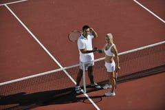 Os pares novos felizes jogam o jogo do tênis ao ar livre Fotos de Stock