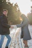 Os pares novos felizes no inverno estacionam guardar-se mão Imagem de Stock Royalty Free