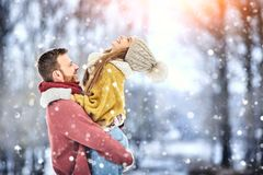 Os pares novos felizes no inverno estacionam o riso e ter do divertimento Família ao ar livre imagem de stock
