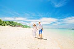 Os pares novos felizes nos chapéus e nos óculos de sol andam em Foto de Stock Royalty Free