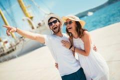 Os pares novos felizes que andam pelo porto de um mar turístico recorrem fotografia de stock