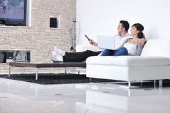 Os pares novos felizes relaxam em casa Fotografia de Stock