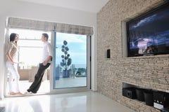 Os pares novos felizes relaxam em casa Imagens de Stock