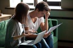 Os pares novos forçados discutem sobre contas em casa foto de stock