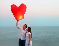 Os pares novos ligam uma lanterna chinesa vermelha do céu no crepúsculo Imagens de Stock