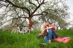 Os pares novos loving com as bicicletas na mola jardinam Fotografia de Stock