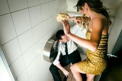 Os pares novos lutam em um partido no toilette Fotos de Stock