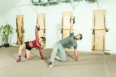 Os pares novos malham o exercício no gym, foco seletivo da aptidão do kettlebell fotografia de stock royalty free