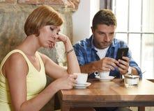 Os pares novos na cafetaria com o viciado do Internet e do telefone celular equipam a ignorância de mulher frustrante fotografia de stock royalty free