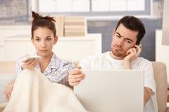 Os pares novos na cama equipam a mulher de funcionamento que presta atenção à tevê Imagens de Stock Royalty Free