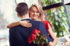 Os pares novos na data na mulher do ramalhete da terra arrendada da dança do restaurante fecharam os olhos alegres imagem de stock royalty free