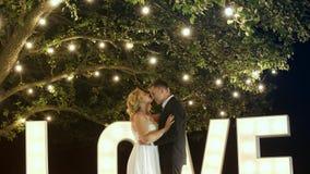 Os pares novos no amor em vestidos de noite estão dançando perto das letras da luz do amor video estoque