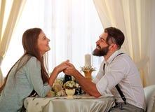 Os pares novos no amor na tabela comemoram o jantar romântico Fotografia de Stock