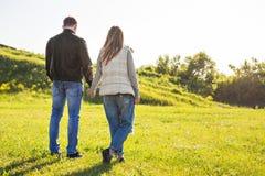 Os pares novos no amor que anda no outono estacionam guardar as mãos que olham no por do sol Imagem de Stock Royalty Free