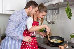 Os pares novos no amor que cozinha junto na cozinha e têm o fu Fotografia de Stock