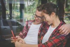Os pares novos no amor sorriem & olham o telefone esperto Homem caucasiano foto de stock royalty free