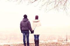Os pares novos no inverno estacionam, as madeiras, descansando apreciando a caminhada, família feliz, relacionamentos do amor do  Fotografia de Stock