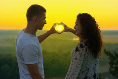 Os pares novos no por do sol fazem uma forma do coração das mãos, dos raios do brilho do sol através das mãos, da paisagem bonita Fotos de Stock Royalty Free