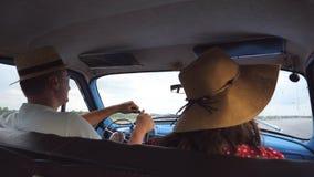 Os pares novos nos chapéus que montam no carro do vintage durante o verão viajam Homem e mulher que sentam-se no assento dianteir filme