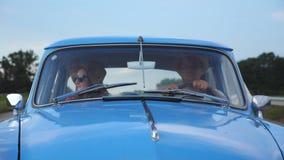 Os pares novos nos chapéus que montam no carro do vintage no verão viajam Homem e mulher que sentam-se no assento dianteiro do ca filme