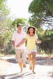 Os pares novos, prendendo as mãos, andando, andam no parque Imagem de Stock