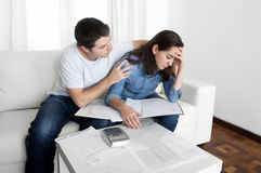 Os pares novos preocuparam-se em casa no marido do esforço que consola a esposa em problemas financeiros Fotografia de Stock Royalty Free