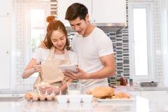 Os pares novos que cozinham junto, mulher primeiramente racham um ovo e põem-no em uma bacia imagens de stock royalty free