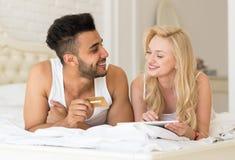 Os pares novos que encontram-se na cama que usa o tablet pc guardam o pagamento em linha da compra do cartão de crédito Fotos de Stock