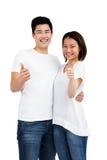 Os pares novos que mostram os polegares levantam o sinal Fotografia de Stock