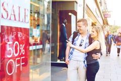 Os pares novos que olham a janela do ` s da loja na cidade com venda adicionam Imagens de Stock