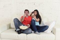 Os pares novos que olham a tevê ostentam a comemoração entusiasmado do jogo de futebol Fotografia de Stock