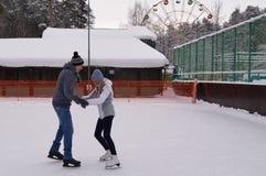 Os pares novos que patinam em uma patinagem no gelo p?blica rink fora na cidade foto de stock