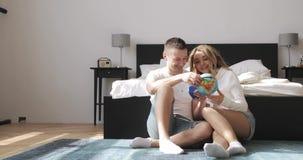Os pares novos que sentam-se ao lado da cama estão olhando o globo que escolhe um lugar viajar na lua de mel Relacionamento do am video estoque