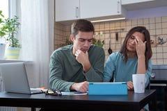 Os pares novos que sentam-se na tabela na cozinha são contratados no planeamento e finanças do cálculo Cara cansado, e emoções ne imagens de stock
