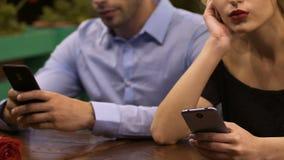 Os pares novos que sentam-se na tabela redigiram em telefones celulares, apego da rede video estoque