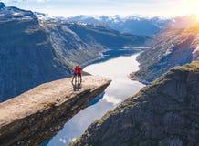 Os pares novos relaxam em Trolltunga A menina feliz aprecia o lago bonito e o bom tempo em Noruega Fotografia de Stock