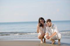 Os pares novos românticos desenharem formas do coração na areia quando na lua de mel Conceito do amor da praia do verão Fotografia de Stock Royalty Free