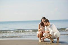 Os pares novos românticos desenharem formas do coração na areia quando na lua de mel Conceito do amor da praia do verão Imagens de Stock Royalty Free