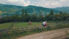 Os pares novos sentam-se junto na cerca perto das montanhas Tempo nebuloso do verão Tiro do ar vídeos de arquivo
