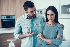 Os pares novos têm o desacordo na cozinha em casa fotografia de stock