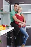 Os pares novos têm o divertimento na cozinha moderna Foto de Stock