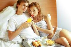 Os pares novos têm o pequeno almoço na cama Foto de Stock Royalty Free