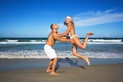Os pares novos têm uma estadia do divertimento na praia Imagens de Stock